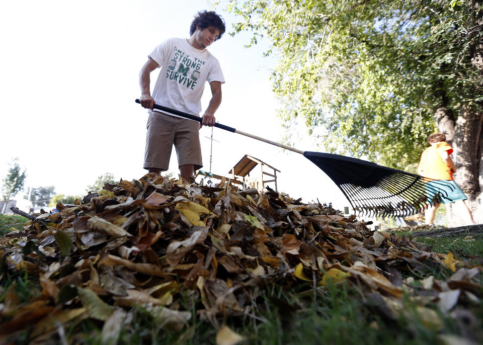 Bishop McGuinness senior  Mike Cardenas rakes leaves as part of a community service project at The Sanctuary women's development center in Oklahoma City. <strong>SARAH PHIPPS - SARAH PHIPPS</strong>