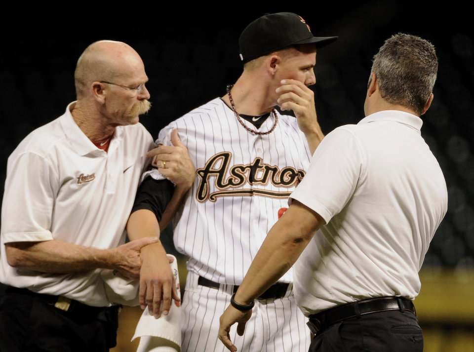 Photo -   Houston Astros trainers help relief pitcher Mickey Storey, center, off the field after he was hit by a line drive from Chicago Cubs' Dave Sappelt in the eighth inning of a baseball game Wednesday, Sept. 12, 2012, in Houston. (AP Photo/Pat Sullivan)