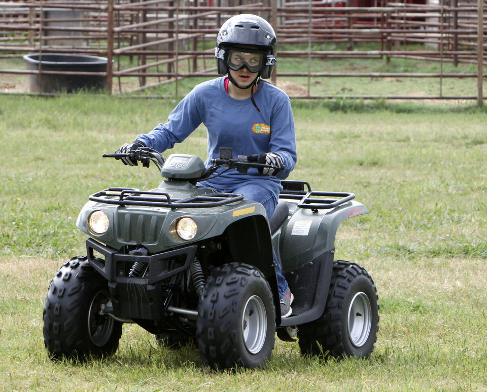 Photo - Thirteen-year-old Emily Brown takes a curve during a children's ATV safety course at the Logan County Fairgounds in Guthrie, OK, Friday, May 25, 2012,  By Paul Hellstern, The Oklahoman