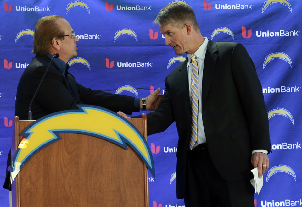 Photo - New San Diego Chargers head coach Mike McCoy, right, shakes hands with President Dean Spanos during an NFL football news conference, Tuesday, Jan. 15, 2013, in San Diego. The former offensive coordinator for the Denver Broncos replaces Norv Turner, who was fired along with general manager A.J. Smith after the Chargers finished 7-9 and missed the playoffs for the third straight season. (AP Photo/Gregory Bull)