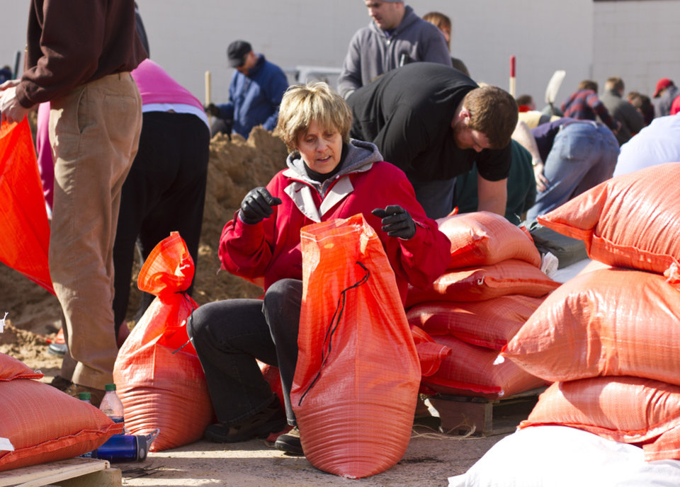 Photo - Sue Chapla helps with sand bags Sunday, April 21, 2013 at the city's public works facility on Market street in Grand Rapids, Mich. (AP Photo/The Grand Rapids Press, Sally Finneran)