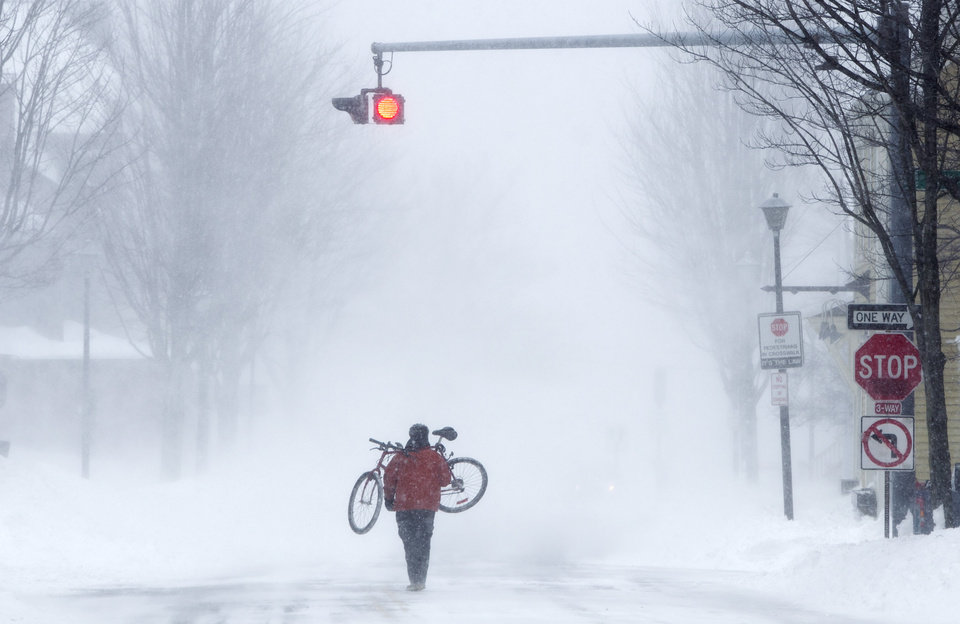 Photo - Juan Tavares carries his bike rather than risk riding on a snow-covered street during a blizzard, Saturday, Feb. 9, 2013, in Portland, Maine. The storm dumped more than 30 inches of snow as of Saturday afternoon, breaking the record for the biggest storm on record. (AP Photo/Robert F. Bukaty)