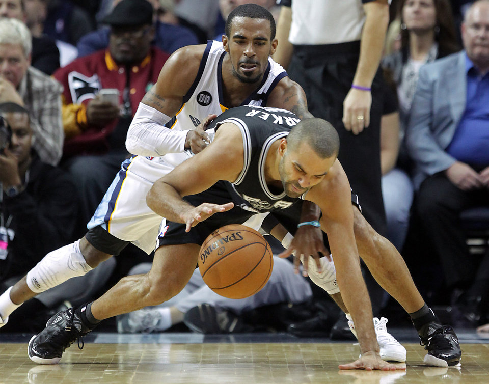Photo - Memphis Grizzlies guard Mike Conley, top, tries to steal the ball from San Antonio Spurs guard Tony Parker in the second half of an NBA basketball game on Friday, Jan. 11, 2013, in Memphis, Tenn. Memphis won in overtime 101-98. (AP Photo/Lance Murphey)