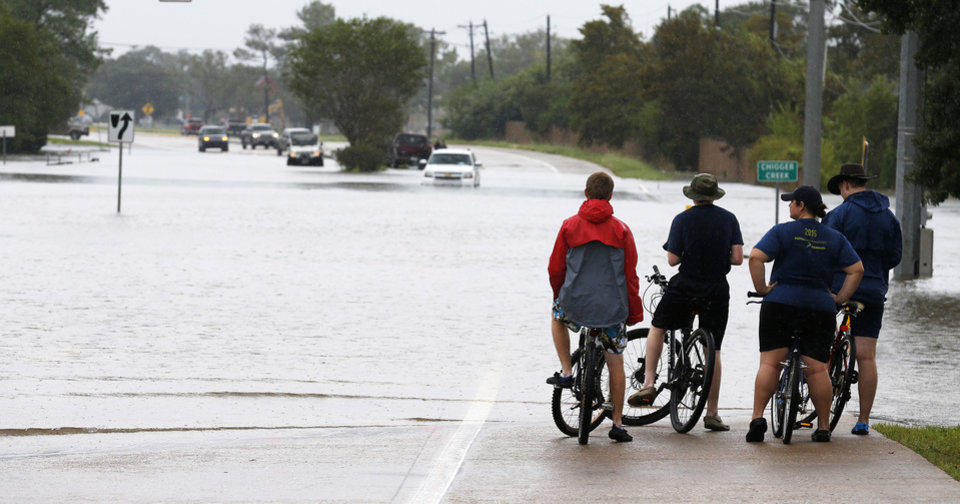 Photo - Residents survey the flood waters in Friendswood, Texas, Sunday, Aug. 27, 2017. (Kevin M. Cox/The Galveston County Daily News via AP)
