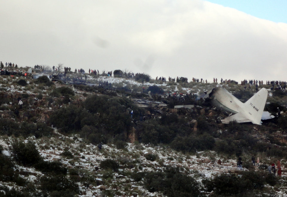 Photo - People look at the wreckage of Algerian military transport plane after it slammed into a mountain in the country's rugged eastern region, Tuesday, Feb. 11, 2014. A civil defense official said 102 people on board were killed but one person managed to survive. The U.S.-built C-130 Hercules transport crashed about noon near the town of Ain Kercha, 50 kilometers (30 miles) southeast of Constantine, the main city in eastern Algeria. ( AP Photo/ Mohamed Ali)