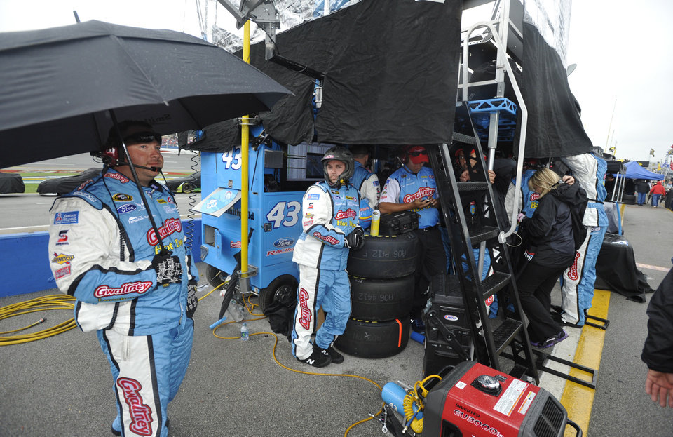 Photo - The pit crew of NASCAR Sprint Cup Series driver Aric Almirola waits for the rain to stop during a rain delayed Aaron's 499 auto race at Talladega Superspeedway in Talladega, Ala., Sunday, May 5, 2013. (AP Photo/Rainier Ehrhardt)