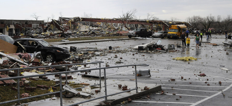 The remains of the Henryville High school are examined by firefighters and residents of Henryville following severe storms that went through the area, Friday, March 2, 2012, in Henryville, Ind. Tornadoes ripped across several small southern Indiana towns on Friday, killing at least three people and leaving behind miles of flattened devastation along the border with Kentucky. (AP Photo/Timothy D. Easley) ORG XMIT: KYTE103