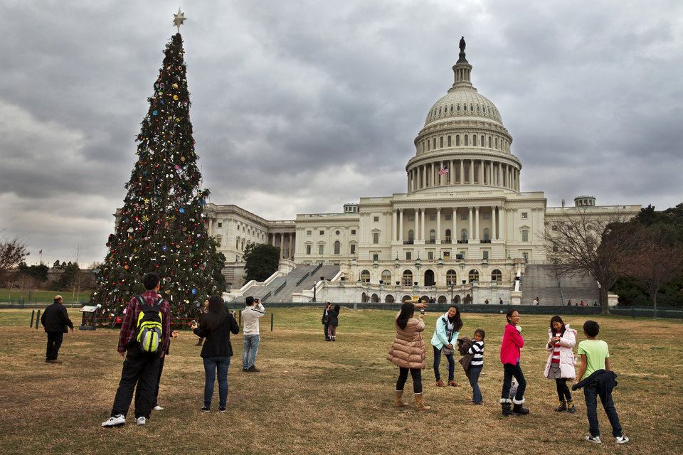 Photo - Under rolling clouds, tourists remove their jackets as they visit the U.S. Capitol Christmas tree in Washington, Sunday, Dec. 22, 2013. Unseasonably warm temperatures in the low 70's are expected Sunday in the Washington region, with rain likely. Temperatures are expected to dip down to the 30's and 40's later in the week, according to the National Weather Service. (AP Photo/Jacquelyn Martin)
