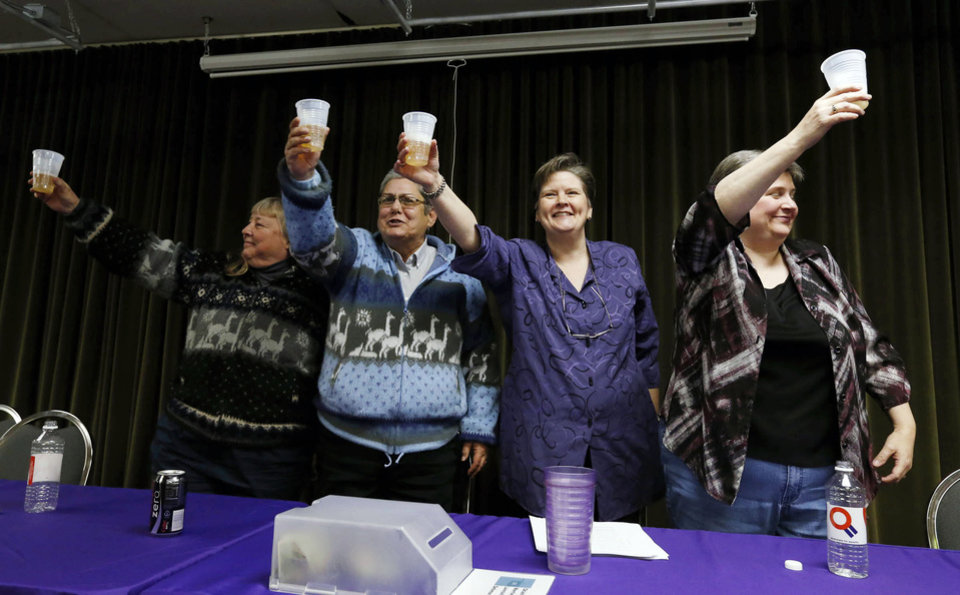Photo - FILE - In this Tuesday, Jan. 14, 2014, file photo, Gay Phillips, left, her partner Sue Barton, along with Mary Bishop and her partner Sharon Baldwin, right, toast during a celebration at the Dennis R. Neill Equality Center, in Tulsa, Okla., after a federal judge struck down Oklahoma's gay marriage ban. But the judge headed off any rush to the altar by setting aside his order while state and local officials complete an appeal. In less than a month, two federal judges have struck down state bans on gay marriage for the same reason, concluding that they violate the Constitution's promise of equal treatment under the law. Although that idea has been the heart of the gay marriage debate for years, the decisions in deeply conservative Oklahoma and Utah offer new momentum for litigants pressing the same argument in dozens of other cases across the country. (AP Photo/Tulsa World,  James Gibbard, File)