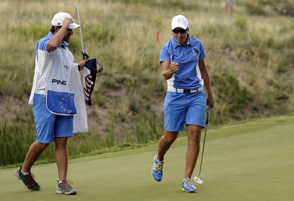 Photo - Europe's Carlota Ciganda, from Spain, celebrates with her caddie Javier Urquizu after she defeated United States' Morgan Pressel in their singles match at the Solheim Cup golf tournament, Sunday, Aug. 18, 2013, in Parker, Colo. (AP Photo/Chris Carlson)