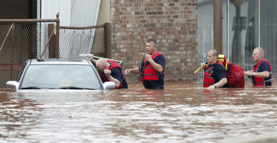 Oklahoma City firefighters rescue a motorist after he ignored a roadblock and drove in to flood waters on SW 29th near Robinson in Oklahoma City, July 8 , 2010. Photo by Steve Gooch, The Oklahoman