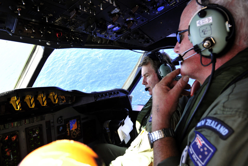 Photo - Royal New Zealand Air Force (RNZAF) co-pilot and squadron leader Brett McKenzie, left, and flight engineer Trent Wyatt sit in the cockpit aboard a P-3 Orion en route to search the southern Indian Ocean for missing Malaysia Airlines Flight 370, Friday, April 11, 2014. Authorities are confident that signals detected in the ocean are from the jet's black boxes, Australian Prime Minister Tony Abbott said, raising hopes they are close to solving one of aviation's most perplexing mysteries. (AP Photo/Richard Polden, Pool)