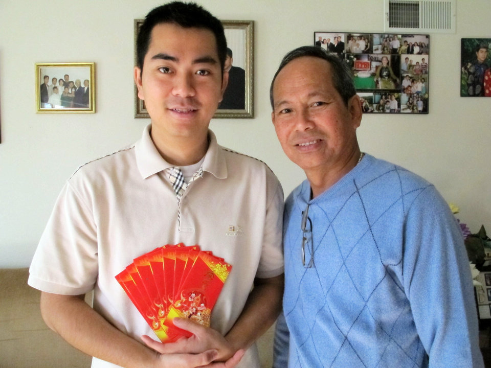Photo - This Jan. 2, 2014 photo shows Billy Le, 26, and his father Tong Le, 61, in their Garden Grove, calif., home holding the slender red envelopes used to give out lucky money to family and friends during the Vietnamese Lunar New Year. The Vietnamese community in Orange County's Little Saigon will celebrate starting Jan. 31 with festivals, firecrackers and special foods. (AP Photo/Amy Taxin)
