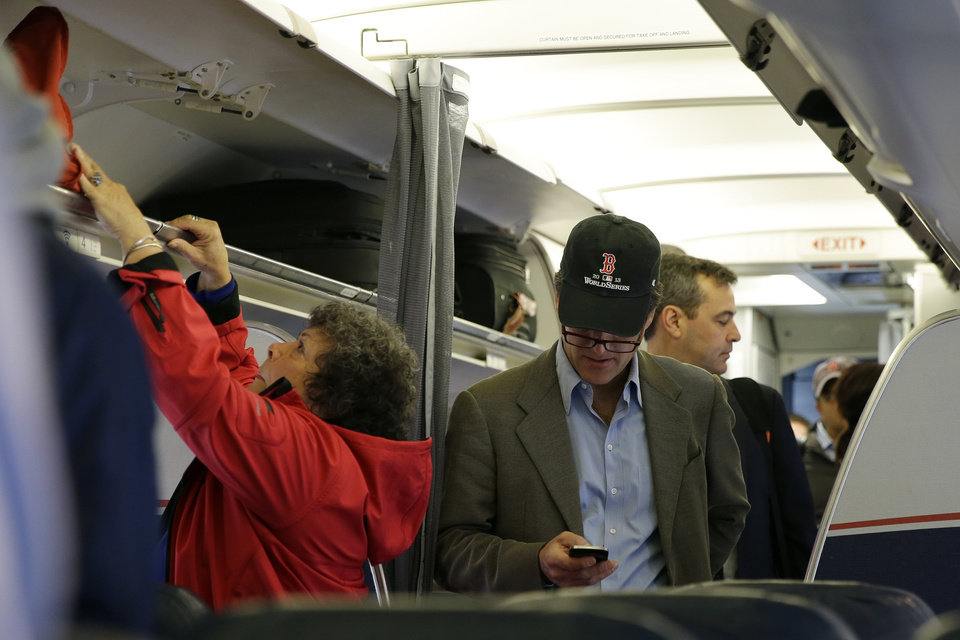 Photo - A passenger check his cell phone while boarding a flight, Thursday, Oct. 31, 2013, in Boston. The Federal Aviation Administration issued new guidelines Thursday, under which passengers will be able to use devices to read, work, play games, watch movies and listen to music, from the time they board to the time they leave the plane. (AP Photo/Matt Slocum)