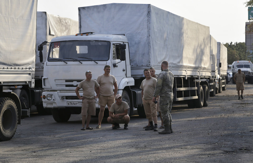 Photo - Drivers of the first trucks of the convoy seen in parking the city of Luhansk, eastern Ukraine, Friday, Aug. 22, 2014.  The first trucks in a Russian aid convoy crossed into eastern Ukraine on Friday after more than a week's delay. (AP Photo/Sergei Grits)