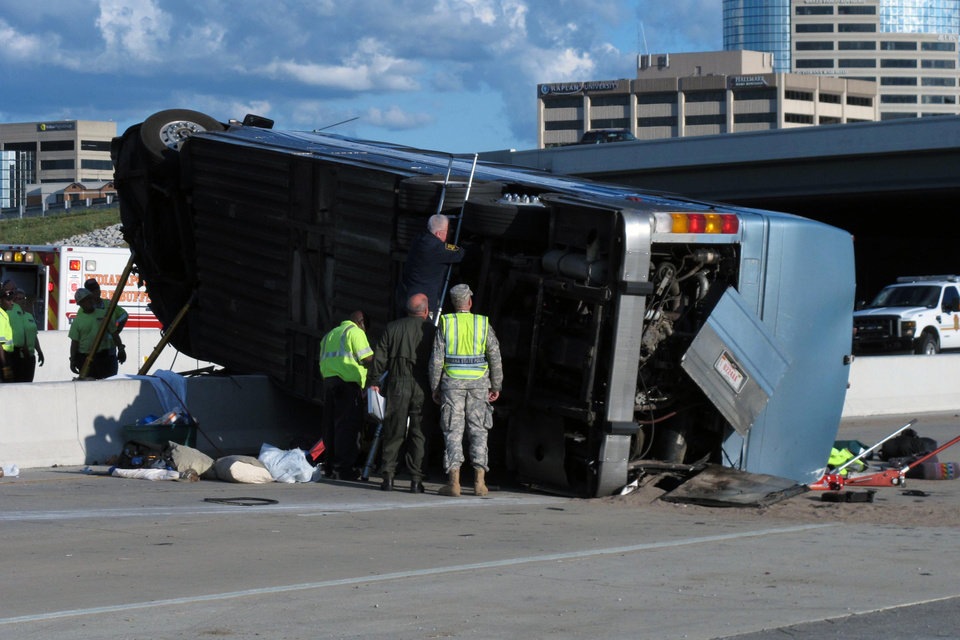 Indiana State Police investigators inspect the underside of a bus that crashed Saturday, July 27, 2013, on Indianapolis' far north side while carrying teenagers returning from a summer camp in Michigan. Three people were killed and 26 others were taken to local hospitals following the crash, which occurred when the bus exited an interstate ramp and crashed into a concrete retaining wall. Investigators don't yet know what caused the crash about a mile from its destination, Colonial Hills Baptist Church. (AP Photo/Rick Callahan)