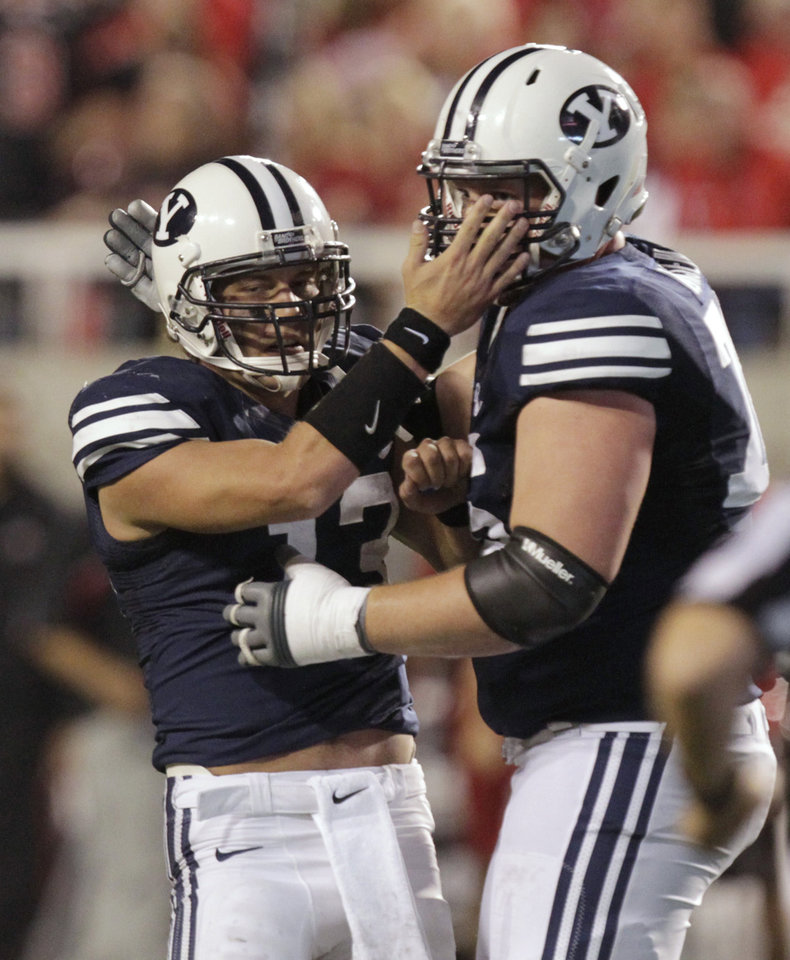 Photo -   BYU quarterback Riley Nelson, left, is congratulated by offensive linesman Braden Hansen after throwing a touchdown pass during the second quarter of an NCAA college football game against Utah on Saturday, Sept. 15, 2012, in Salt Lake City. (AP Photo/Rick Bowmer)