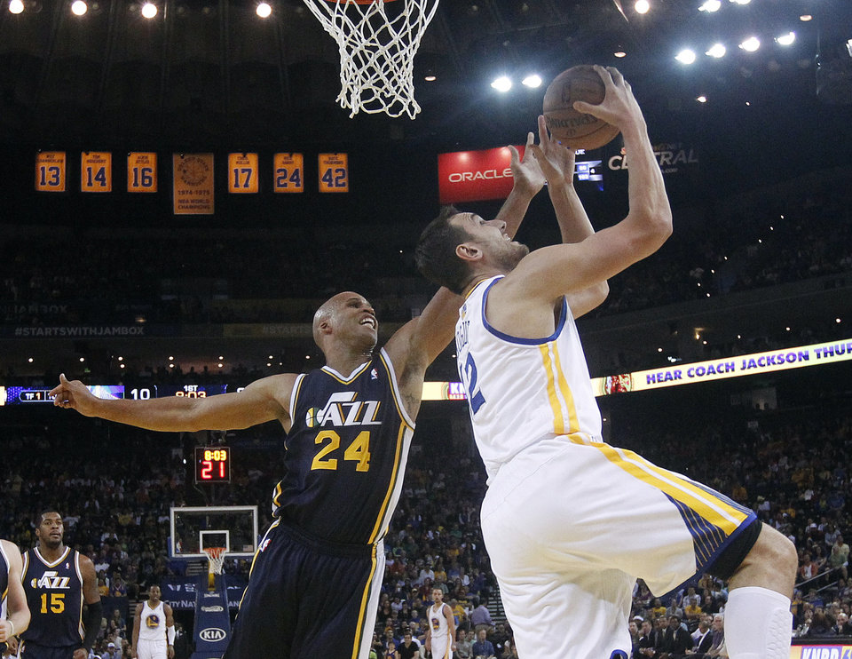 Photo - Golden State Warriors center Andrew Bogut, right, shoots next to Utah Jazz forward Richard Jefferson (24) during the first half of an NBA basketball game Sunday, April 6, 2014, in Oakland, Calif. (AP Photo/Marcio Jose Sanchez)