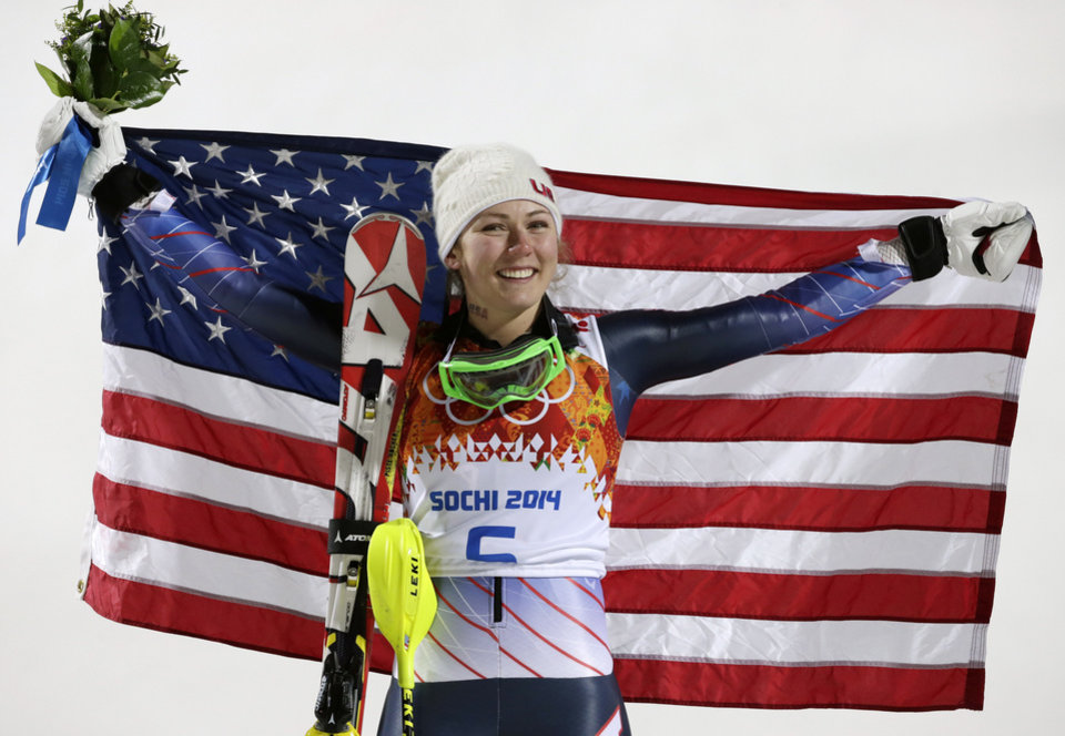 Photo - Women's slalom gold medal winner Mikaela Shiffrin of the United States poses for photographers with the U.S. flag at the Sochi 2014 Winter Olympics, Friday, Feb. 21, 2014, in Krasnaya Polyana, Russia.(AP Photo/Gero Breloer)