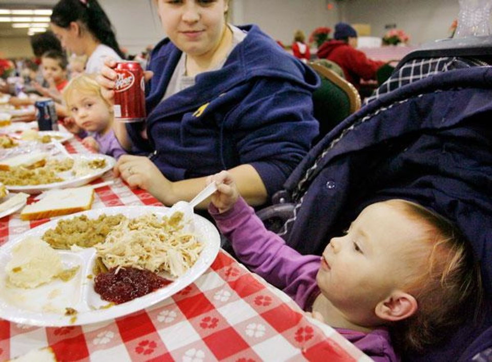 Photo -  Reaching up from her seat in her stroller, Hannah Thomas, 1 1/2, feels her way for another bite of food at the annual Red Andrews Christmas Dinner at the Cox Convention Center in downtown Oklahoma City, Thursday, Dec. 25, 2008.  She was there with her mother, Shelby Thomas, Oklahoma City. BY JIM BECKEL, THE OKLAHOMAN
