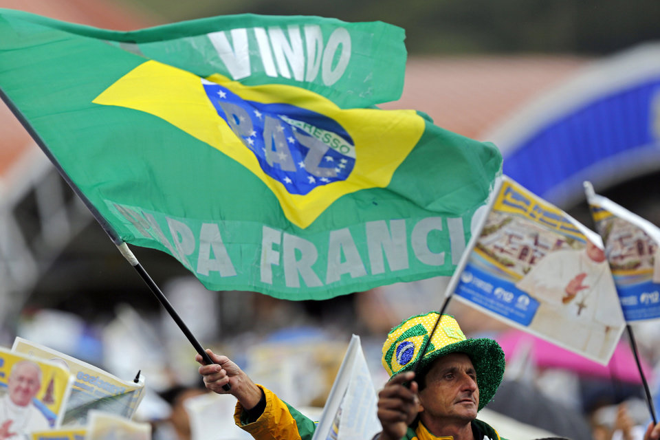 Photo - A pilgrim waves a Brazilian flag covered with the Portuguese words