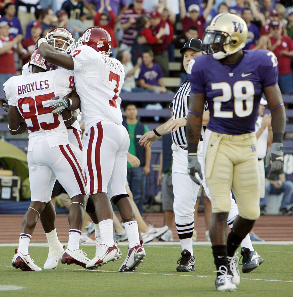 Photo - OU's Ryan Broyles (65), Juaqin Iglesias (9) and DeMarco Murray (7) celebrate a touchdown reception by Iglesias in the first quarter as UW's Quinton Richardson (28) walks away during the college football game between Oklahoma and Washington at Husky Stadium in Seattle, Wash., Saturday, September 13, 2008. BY NATE BILLINGS, THE OKLAHOMAN