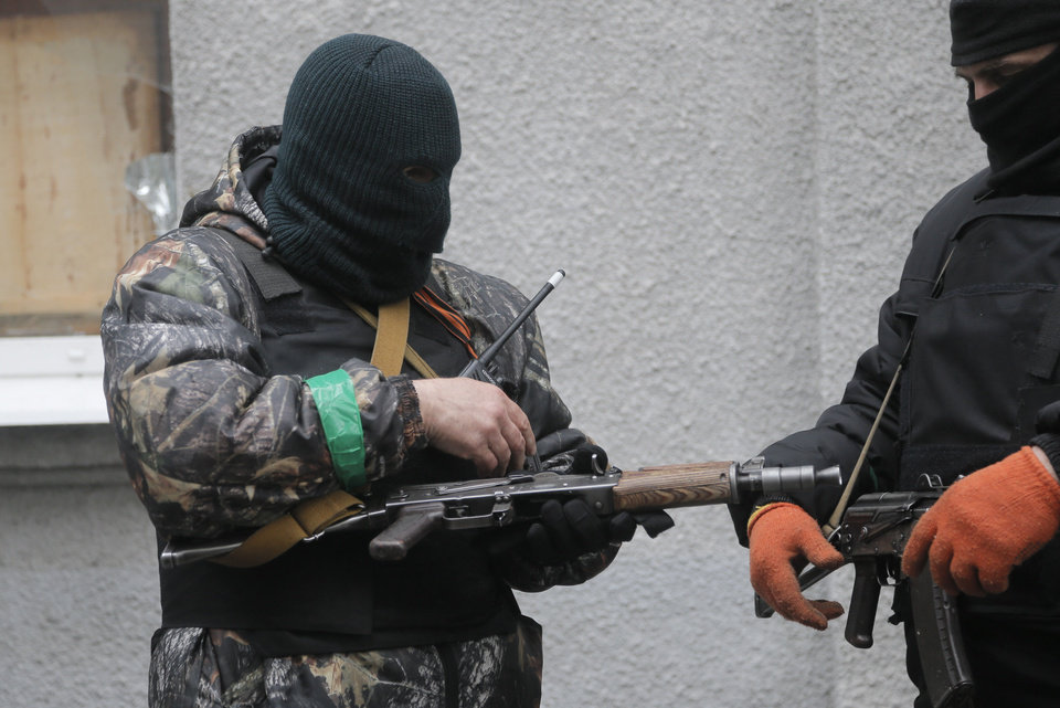 Photo - Pro-Russian gunmen check their weapons at a seized police station in the eastern Ukrainian town of Slovyansk on Sunday, April 13, 2014. Ukrainian special forces exchanged gunfire with a pro-Russia militia in the eastern city Sunday, according to the interior minister, who said one Ukrainian security officer was killed and five others wounded. It was the first reported gunbattle in east Ukraine, where armed pro-Russia men have seized a number of law enforcement buildings in recent days. (AP Photo/Efrem Lukatsky)