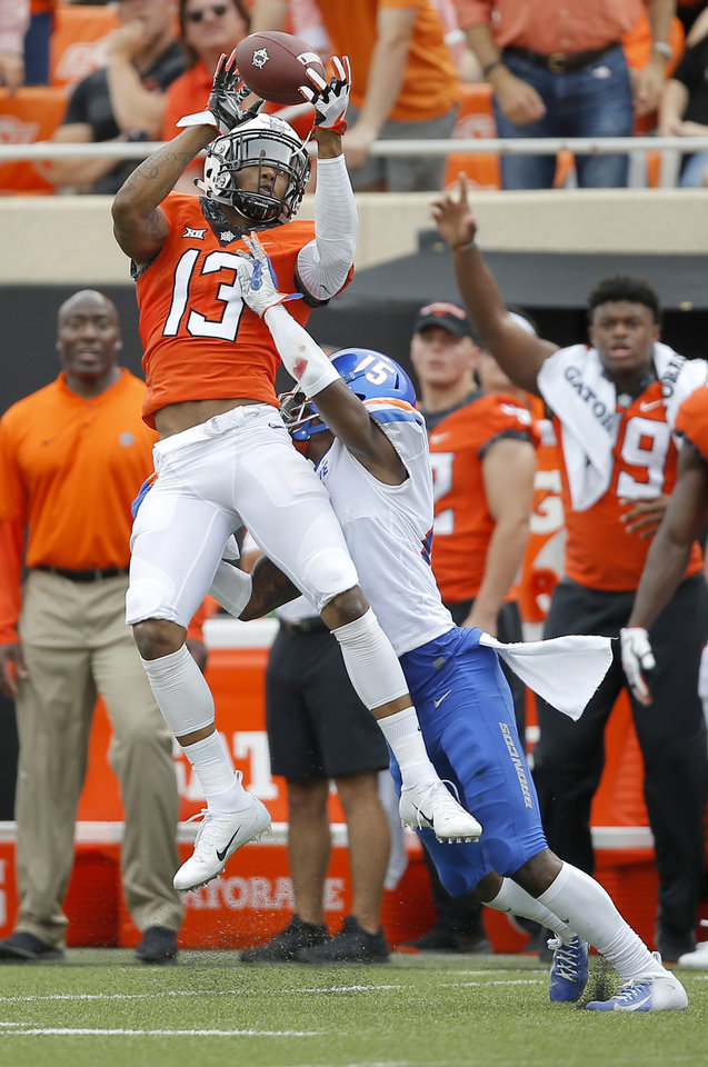 Photo - Oklahoma State's Tyron Johnson (13) catches the ball over Boise State's Jalen Walker (15) during a college football game between the Oklahoma State University Cowboys (OSU) and the Boise State Broncos at Boone Pickens Stadium in Stillwater, Okla., Saturday, Sept. 15, 2018. Photo by Bryan Terry, The Oklahoman
