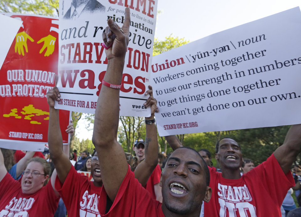 Photo - Hundreds of protesters gather outside of the McDonald's Corporation Thursday, May 22, 2014, in Oak Brook, Ill., demonstrating for a $15 an hour wage and the right to unionize. The group gathered outside the entrance as the company held the annual shareholders meeting. (AP Photo/M. Spencer Green)