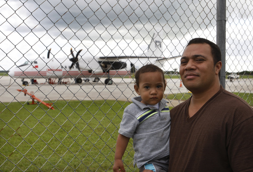 Photo - In this Wednesday, June 4, 2014 photo, Sau Tongi, holding his son, stands in front of a China-made MA-60 plane on the tarmac at Fua'amotu Domestic Airport in Nuku'alofa, Tonga. New Zealand tourists attracted by the country's beauty have been staying away due to a dispute over the safety of the plane. The dispute represents a small skirmish in a broader battle for global influence. (AP Photo/Nick Perry)