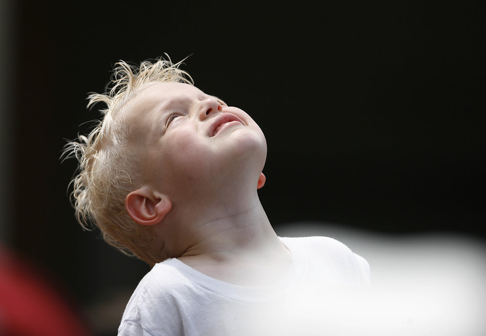 Easton Witters, 3, of Oklahoma City, looks up to let rain drops fall on his face during a Women's College World Series game between Oklahoma University and Arizona State University at ASA Hall of Fame Stadium in Oklahoma City, Sunday, June 3, 2012.  Photo by Garett Fisbeck, The Oklahoman