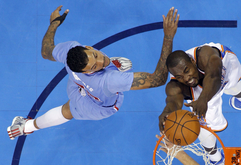 Photo - Oklahoma City 's Serge Ibaka (9) thinks as Los Angeles' Matt Barnes (22) defends during the NBA game between the Oklahoma City Thunder and the Los  Angeles Clippers at the Chesapeake Energy Arena, Sunday, Feb. 23, 2014. Photo by Sarah Phipps, The Oklahoman