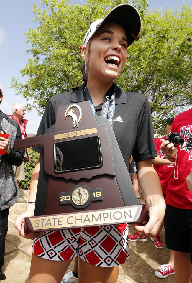 Photo -  Purcell's ShaeBug Scarberry wears her championship medal and carries the Class 3A team championship trophy Thursday at Westwood Park Golf Course in Norman. [Photo by Steve Sisney, The Oklahoman]