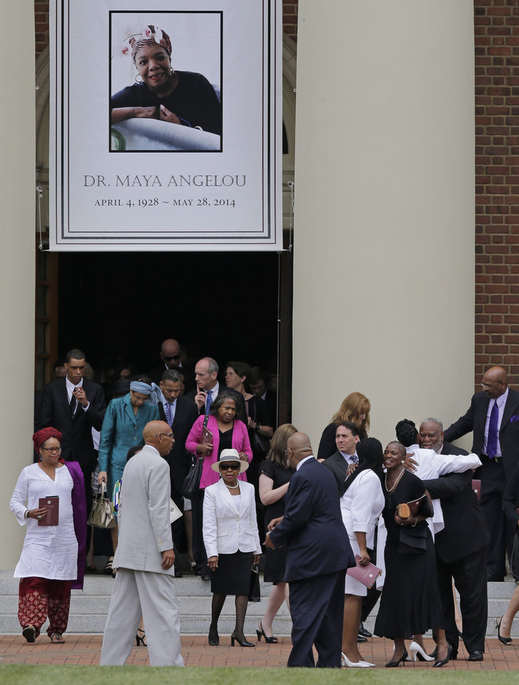 Photo - Mourners hugs outside Wait Chapel after a memorial service for poet and author Maya Angelou at Wait Chapel. at Wake Forest University in Winston-Salem, N.C., Saturday, June 7, 2014. Former President Bill Clinton and Oprah Winfrey joined First Lady Michelle Obama at the service. (AP Photo/Chuck Burton)