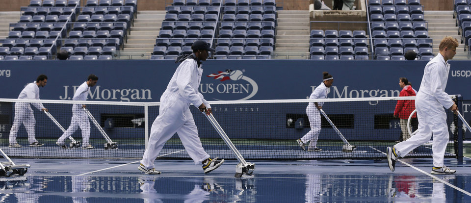 Photo - FILE - In this Sept. 8, 2012, file photo, workers clear water from the court at Arthur Ashe Stadium for a semifinal match at the 2012 US Open tennis tournament in New York. After all the rain in recent years, the first significant steps have been taken toward putting a retractable roof on Arthur Ashe Stadium; it's supposed to be ready for the 2016 U.S. Open. (AP Photo/Charles Krupa, File)