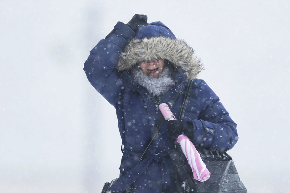 Photo - A woman holds onto her hood as the wind blows during a winter snowstorm Tuesday, Jan. 21, 2014, in Philadelphia. A storm is sweeping across the Mid-Atlantic and New England. The National Weather Service said the storm could bring 8 to 12 inches of snow to Philadelphia and New York City, and more than a foot in Boston.  (AP Photo/Matt Rourke)