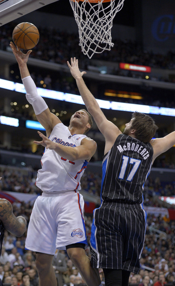 Los Angeles Clippers  forward Blake Griffin, left, puts up a shot as Orlando Magic  forward Josh McRoberts defends during the first half of their NBA basketball game, Saturday, Jan. 12, 2013, in Los Angeles. (AP Photo/Mark J. Terrill)
