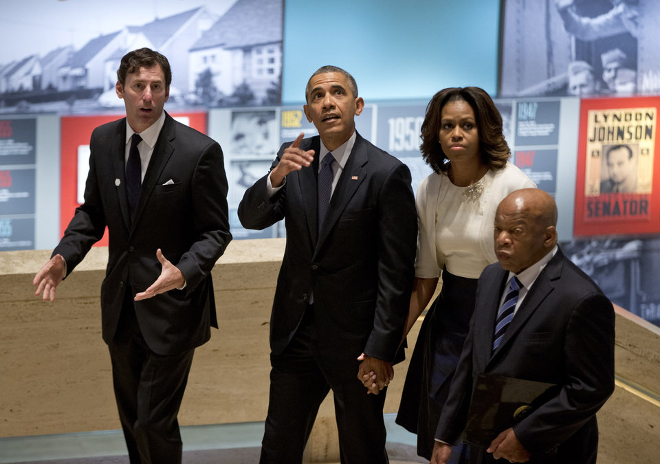 Photo - From left, LBJ Presidential Library Director Mark Updegrove, President Barack Obama, first lady Michelle Obama and Rep. John Lewis, D-Ga., arrive in the Great Hall at the LBJ Presidential Library in Austin, Texas, Thursday, April 10, 2014, to attend a Civil Rights Summit to commemorate the 50th anniversary of the signing of the Civil Rights Act. (AP Photo/Carolyn Kaster)