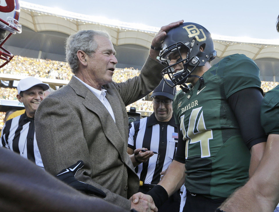 Photo - Former President George W. Bush, left, pats Baylor quarterback Bryce Petty (14) on the head after the coin toss before the NCAA college football game between SMU and Baylor Sunday, Aug. 31, 2014, in Waco, Texas. (AP Photo/LM Otero)