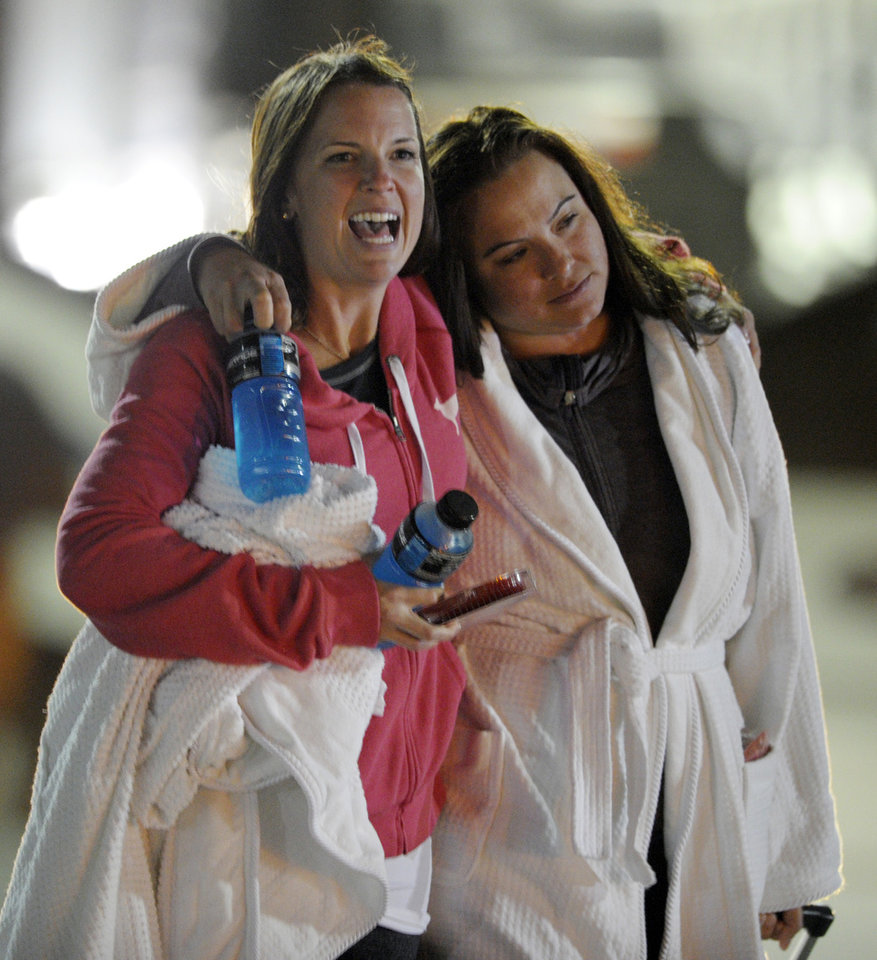 Photo - Kristina Courson, left, of Paris, Texas, is embraced by Jamie Hilliard, of Denison, Texas, after getting off the cruise ship Carnival Triumph in Mobile, Ala., Thursday, Feb. 14, 2013. The ship with more than 4,200 passengers and crew members has been idled for nearly a week in the Gulf of Mexico following an engine room fire. (AP Photo/G M Andrews)