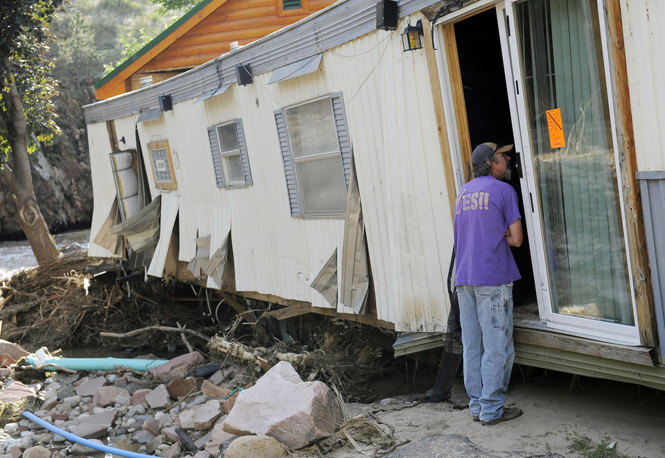 Photo - Dirk Huntington checks on a friend's flood-damaged trailer at the River Bend Mobile Home Park in Lyons, Colo., on Thursday, Sept. 19, 2013. Hundreds of evacuees were allowed past National Guard roadblocks Thursday to find a scene of tangled power lines, downed utility poles, and mud-caked homes and vehicles. (AP Photo/Chris Schneider)