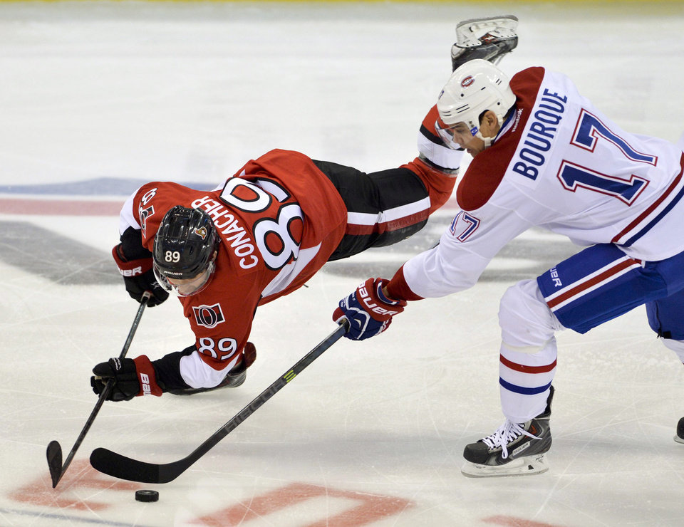 Photo - Montreal Canadiens left wing Rene Bourque and Ottawa Senators left wing Cory Conacher vie for the puck during the first period of an NHL hockey game Thursday, Jan. 16, 2014, in Ottawa, Ontario. (AP Photo/The Canadian Press, Adrian Wyld)