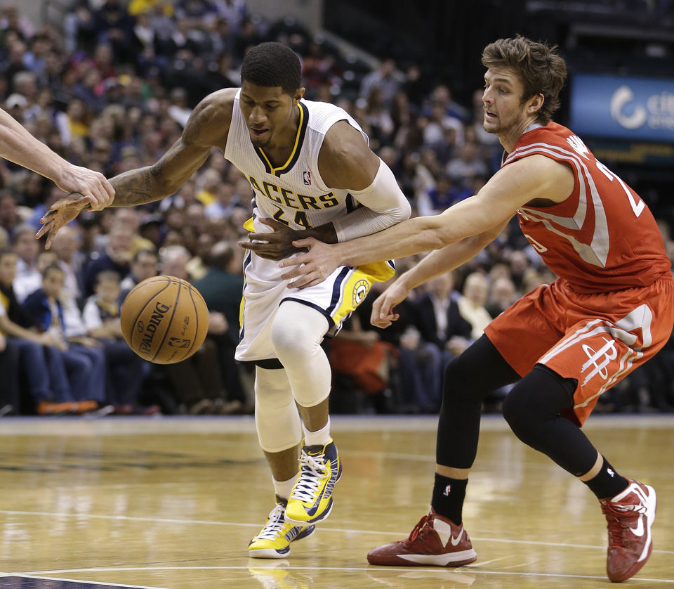 Photo - Indiana Pacers' Paul George (24) is defended by Houston Rockets' Chandler Parsons (25) during the second half of an NBA basketball game Friday, Jan. 18, 2013, in Indianapolis. The Pacers defeated the Rockets 104-93. (AP Photo/Darron Cummings)