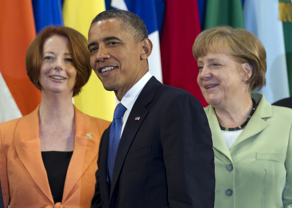 President Barack Obama, center, takes his place with other leaders, including Australian Prime Minister Julia Gillard, left, and German Chancellor Angela Merkel, for the Family Photo during the G20 Summit, Monday, June 18, 2012, in Los Cabos, Mexico. (AP Photo/Carolyn Kaster)
