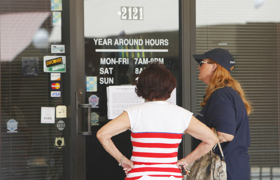 Customers read the closing sign on the Tan & Tone America at 2121 W Edmond Road, Monday, July 23 , 2012.  The company closed all its stores Monday, leaving customers high and dry. Photo By David McDaniel/The Oklahoman