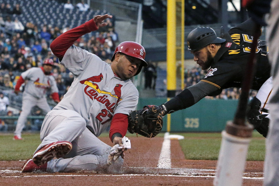 St. Louis Cardinals' Jhonny Peralta (27) slides safely around the attempted tag by Pittsburgh Pirates catcher Russell Martin during the first inning of a baseball game in Pittsburgh on Saturday, April 5, 2014. Peralta scored from third on a sacrifice fly by Allen Craig. (AP Photo/Gene J.Puskar)