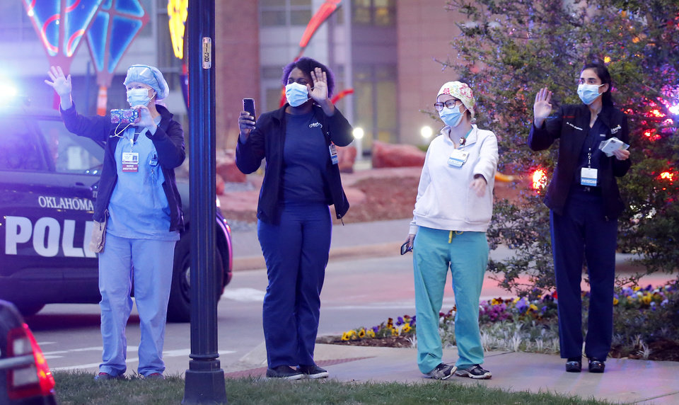 Photo - Medical staff wave to a parade of emergency vehicles during a headlights and flashing lights for Hope at the Chidlren's Hospital in Oklahoma City, Friday, April 3, 2020. The Oklahoma City Police, Oklahoma City Fire Department, OU Police, EMSA, Oklahoma County Sheriffs and Oklahoma City Thunder mascot Rumble paraded around the OU Medical Center to show support for medical staff and patients at the of the Children's Hospital and the campus. [Sarah Phipps/The Oklahoman]