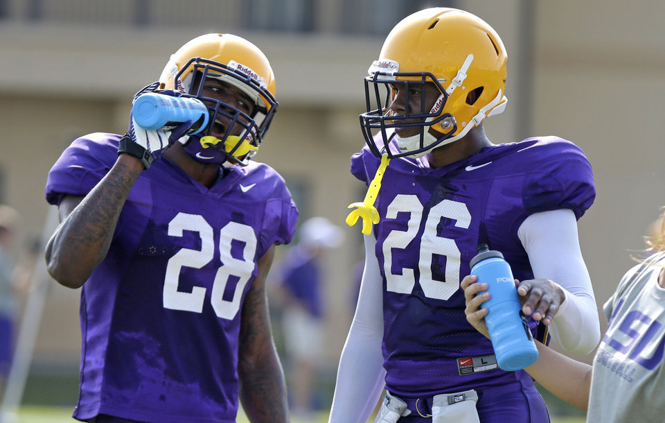 Photo - LSU safety Jalen Mills (28) and safety Ronald Martin (26) drink fluids between drills during their NCAA college football practice in Baton Rouge, La., Wednesday, Aug. 6, 2014. (AP Photo/Gerald Herbert)