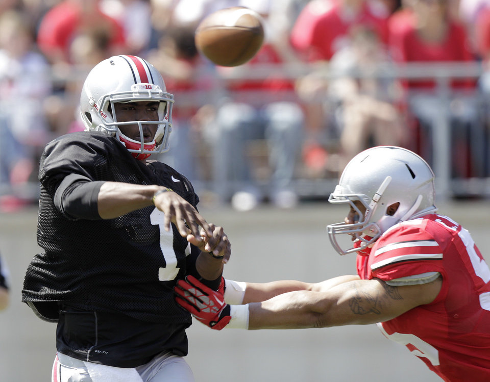 Photo - Ohio State quarterback JT Barrett throws a pass during their spring NCAA college football game Saturday, April 12, 2014, in Columbus, Ohio. (AP Photo/Jay LaPrete)