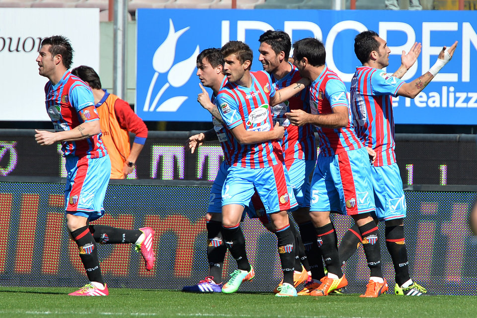 Photo - Catania's Mariano Izco, left, celebrates with his teammates after scoring during the Serie A soccer match between Catania and Lazio at the Angelo Massimino stadium in Catania, Italy, Sunday, Feb. 16, 2014. (AP Photo/Carmelo Imbesi)